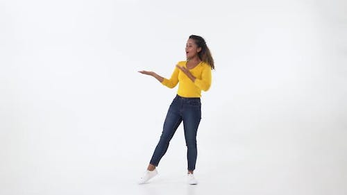Surprised African American young woman open hands to empty space aside left and right