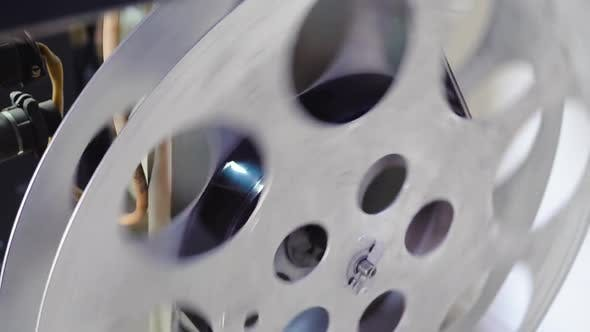 Bobbin with Reel Turns on Vintage Cinema Equipment in Room