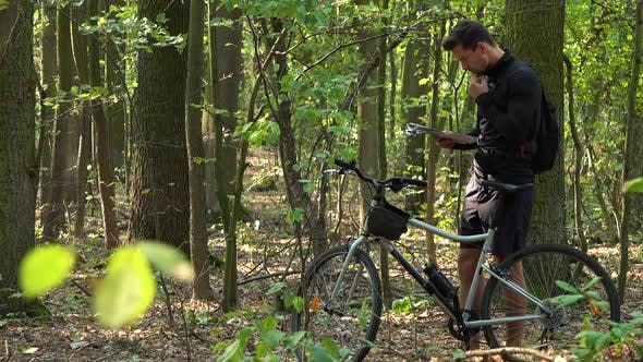 Thumbnail for A Cyclist Stands with a Bicycle in a Forest and Reads a Map