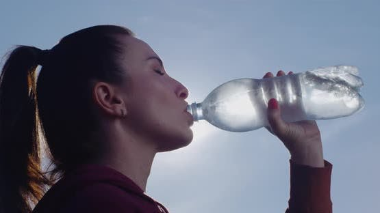 Woman Drinks Water From A Bottle A Close Up Profile Shot With Backlit With Sun And Blue Sky