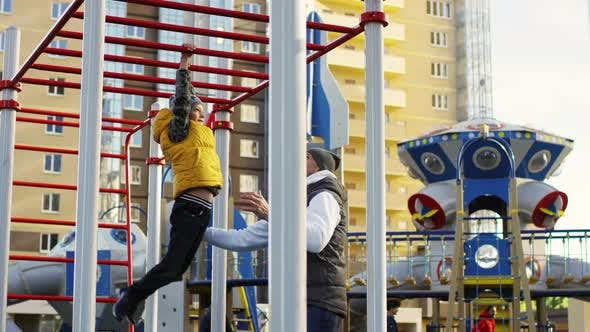 Caucasian Kid Playing on Monkey Bars in Playground