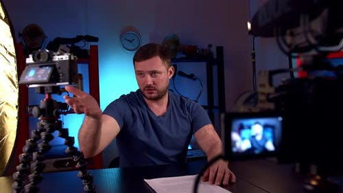 Blogger is Broadcasting in Video Studio with Cameras and Professional Lighting
