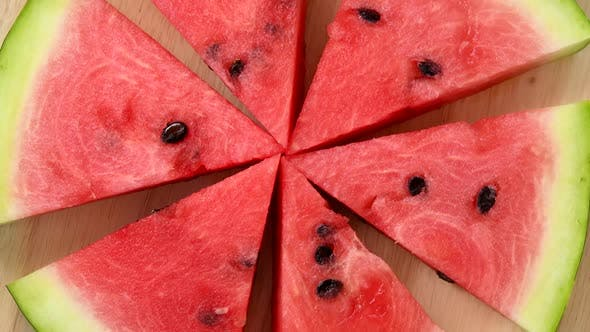 Thumbnail for Slices of watermelon rotating top view on wooden background