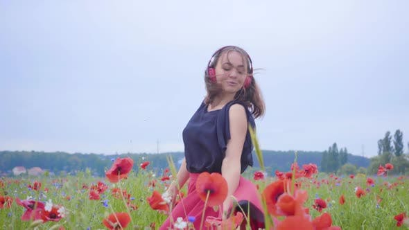 Thumbnail for Cute Young Woman Wearing Headphones Listening To Music and Dancing in a Poppy Field Smiling Happily