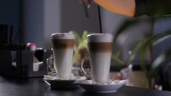 Thumbnail for Hand of Barista Putting Straws in Latte Glasses