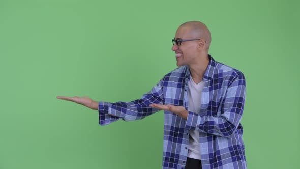 Thumbnail for Happy Bald Hipster Man Showing Something and Looking Surprised
