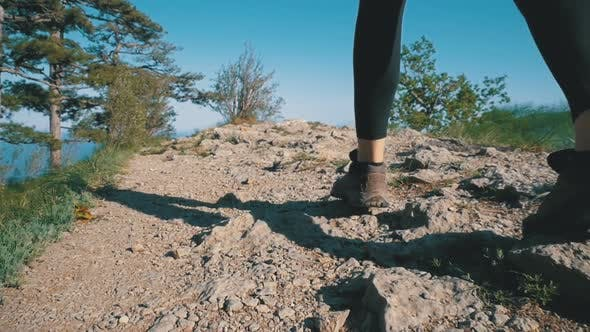 View on Feet of Traveler Woman Hiking Walking on the Top of Cliff in Mountain