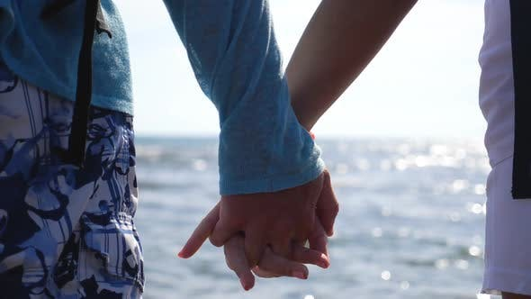 Thumbnail for Young Pair Holding Hands of Each Other Standing on Ocean Coast. Couple of Lovers Resting on Resort