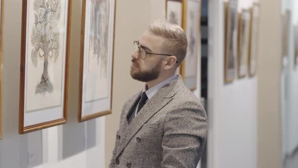 Thumbnail for Man Examining Drawing in Art Gallery