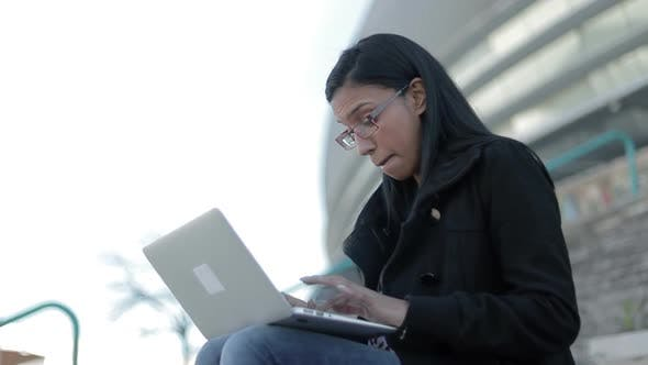 Cover Image for Smiling Hindu Woman in Eyeglasses Typing on Laptop Outdoor