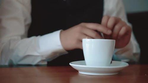 Young Businessman Pours Sugar Into a Mug with Coffee Closeup