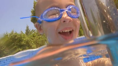 Child wearing goggles diving in the pool
