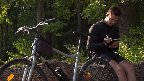 Thumbnail for A Young Handsome Cyclist Sits on a Log Next To His Bike in a Forest and Writes Notes