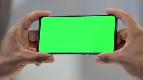 Holding Smartphone with Green Chroma Key Screen