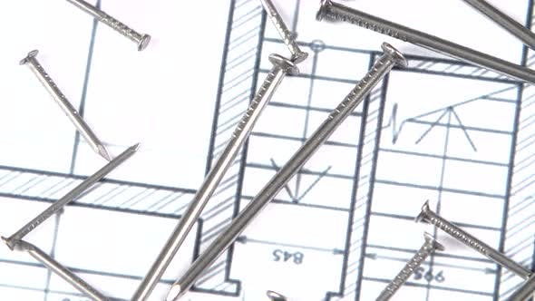 Metal Nails on Building Plan, Close Up, Rotation