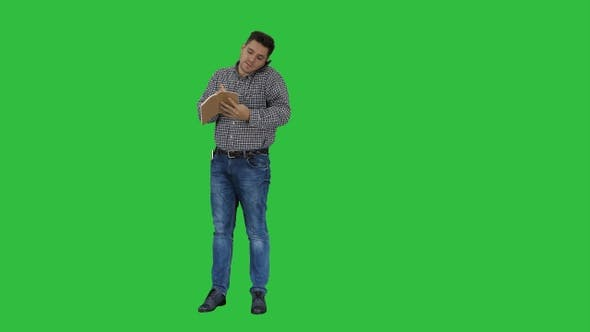 Thumbnail for Man talking on the phone and making notes on a Green Screen