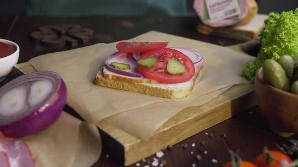 Thumbnail for The Cook Adds Sliced Pickles To the Sandwich with Ham and Vegetables on the Wooden Board in the Beam