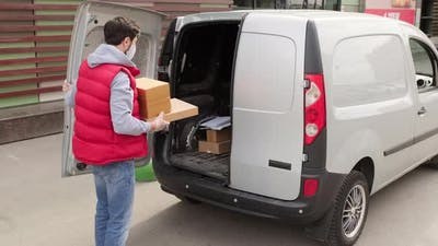 Courier in Face Mask Loading Packages into Van