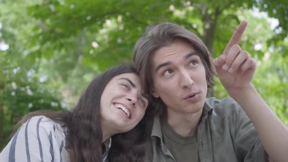 Cover Image for Portrait of a Young Smiling Couple in Casual Clothes Spending Time Together in the Park, Having a