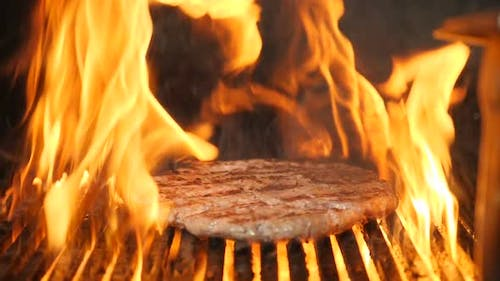 Cooking Meat for Burger on Grill in Slow Motion. Flame Rising Up From Grid. Beautiful Slow Motion
