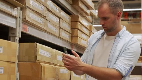Man Scans Boxes of Goods in a Warehouse with a Smartphone