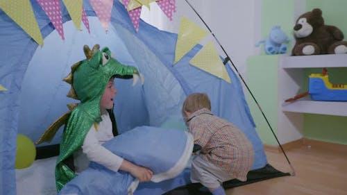 Lustige Kinder, Junge im Karneval Kostüm Viel Spaß mit seinem Bruder spielen Verstecken und Suchen in Wigwam