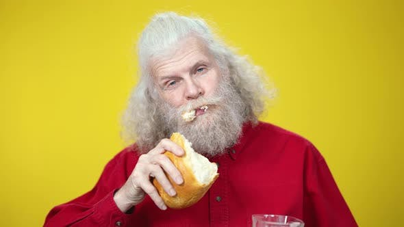 Thumbnail for Closeup Portrait of Confident Senior Man Chewing Bread and Drinking Milk