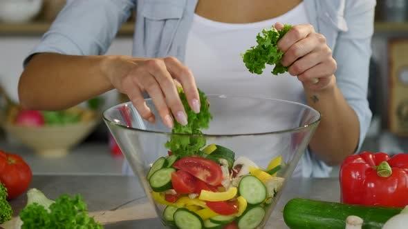 Thumbnail for Zeitlupe der wunderschönen Europäischen Frau mit charmantem Lächeln setzt Salatblätter in eine Glasschale
