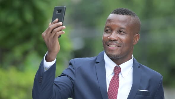 Thumbnail for Young Happy African Businessman Taking Selfie Outdoors