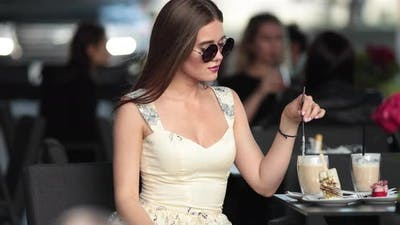 Lovely Girl Drinks Coffee in the Summer Cafe and Wait Someone