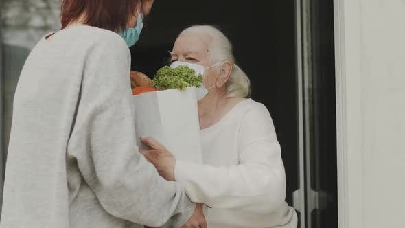 Young Woman In Medical Mask Brought Food To An Elderly Woman During Quarantine