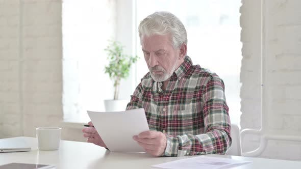 Casual Old Man Reading Documents in Office