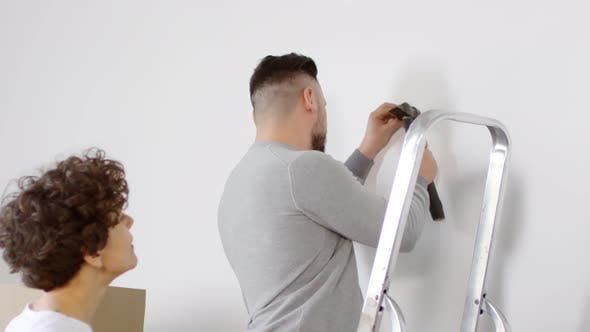 Cover Image for Middle-Aged Man Hammering Nail into White Wall