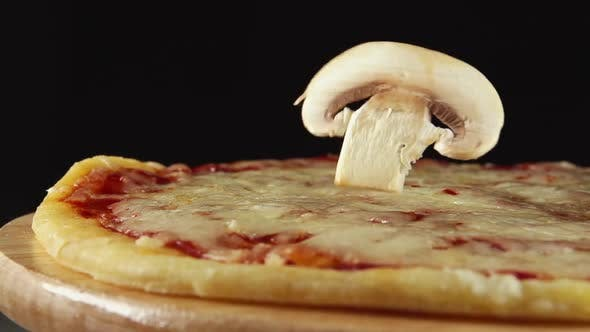 Thumbnail for Mushroom Slice Falls On A Rotating Pizza On A Black Background