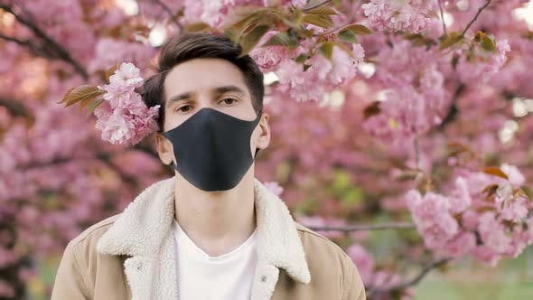 Pandemic, portrait of a young man on a woolen jacket on black virus protective mask on street.