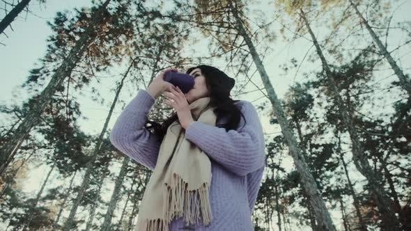 Hübsche Lady im Pullover hält eine Tasse Getränk im Winterwald