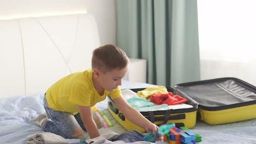 Glückliches Kind legt seine Sachen in einen Koffer. Reisen mit einem Kinderkonzept