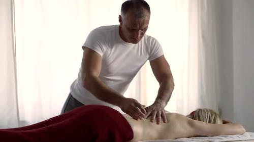 Male Osteopathic Physician Is Massaging Back of Female Patient