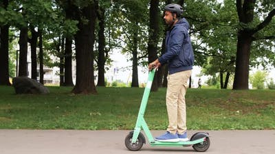 Man in Helmet Riding Electric Scooter on Street