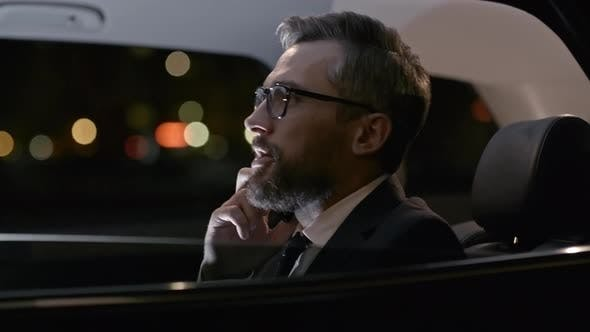 Thumbnail for Man in Suit in Moving Car