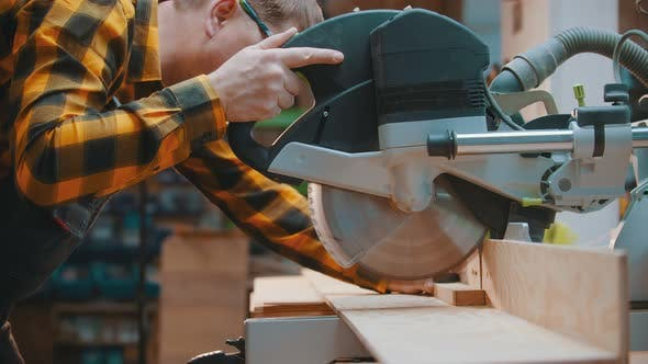 Thumbnail for Carpentry - a Man Woodworker Cutting the Wooden Detail with a Sharp Circular Saw