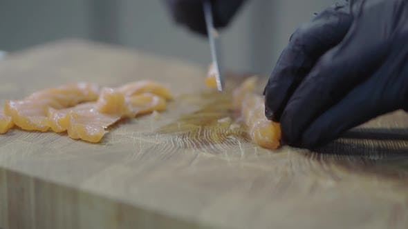 Thumbnail for Chef in Black Rubber Gloves Cutting Salmon on the Wooden Board in Modern Restaurant