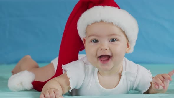 Thumbnail for Funny Little Baby Smiling. Cute Infant Boy Wearing Santa Hat Lying on Sofa