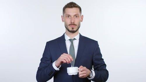 Emotionloser Mann starrt auf Kamera und rührend Kaffee