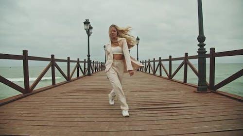 Frau tanzt im Anzug auf Holzsteg