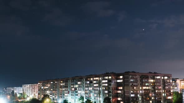 Thumbnail for Stars and Night Clouds Move Over Multi-story Buildings. Night City. Timelapse