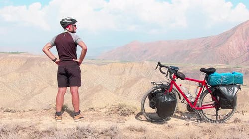 Cyclist Standing By Bicycle In Scenic Mountains(1)