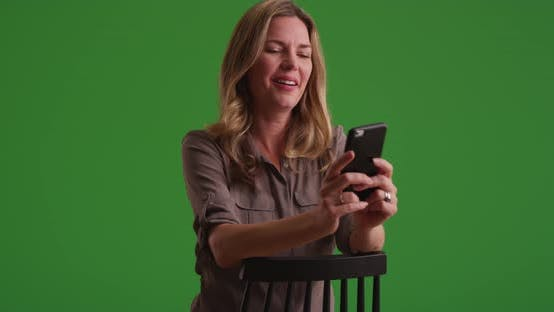 Thumbnail for Middle aged Caucasian woman looking at pictures on smartphone on green screen