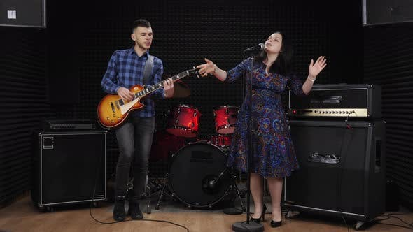 Stylish girl vocalist is singing on stage with man playing guitar