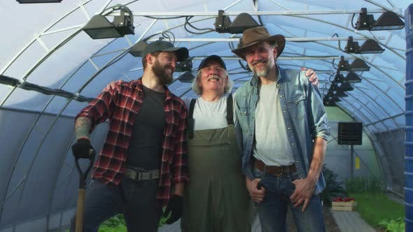 Optimistic Gardeners Hugging in Greenhouse